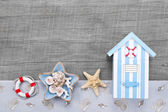 Beach hut and seashells on a grey wooden background for travel concepts — Stock Photo