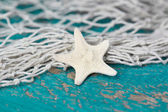 Starfish and fishing net and a turquoise wooden background — Stock Photo