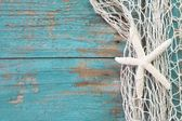 Starfish in a fishing net with a turquoise wooden background sha — Stockfoto