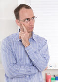 Skeptical man touching chin — Stock Photo