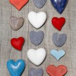 Hearts in different colors on wooden background. — Stock Photo