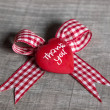 "Red heart with ""thank you"" for a greeting card on checked ribbon — Foto Stock"