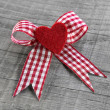 Red heart with a red white checked ribbon for valentines day. — Stockfoto