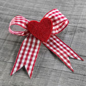 Red heart with a red white checked ribbon for valentines day. — Stock Photo
