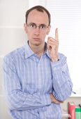 Portrait of serious businessman at office showing his index fing — Stock Photo