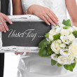 Wedding couple with bridal Bouquet and chalkboard: our day ... — Stock Photo