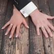 Wedding theme, man and woman hands on a wooden floor — Stock Photo #37373015