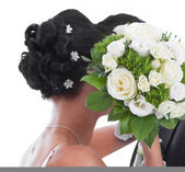 Kissing bride and groom hidden behind bride Bouquet isolated on — Stock Photo