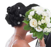 Kissing bride and groom hidden behind bride Bouquet isolated on — Stockfoto