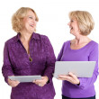 Foto Stock: Two women with tablet and laptop