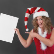 Woman in Santa hat holding blank sign — Stock Photo #37436171