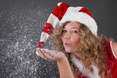Woman blowing snowflakes — Stock Photo
