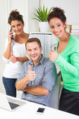 People showing thumbs up in office — Stock Photo