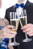 Carnival: young couple isolated on white drinking champagne — ストック写真