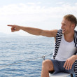 Blond handsome young man on a sailing boat pointing at something — Stock Photo #39962039