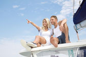 Attractive couple sitting on sailing boat - love. — Stockfoto