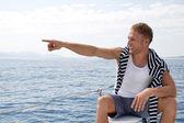 Blond knappe jonge man op een zeilboot wijzend op iets — Stockfoto