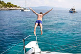 Young man jumping from a sailing boat. — Stock Photo
