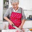 Stock Photo: Senior or older womwith grey hair cooking in kitchen.