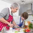 Stockfoto: Grandmother teaching young boy to cook meat-family life at home.