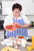 Overweight woman posing in the kitchen with a plate of meats. — Stock Photo
