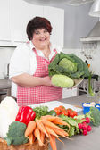 Overweight woman holding salads - cooking at home. — Stock Photo
