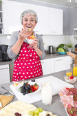 Senior or older woman with grey hair cooking in kitchen. — Stock Photo