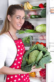 Young woman holding salad in front of her open fridge. — Stock Photo
