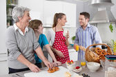 Happy family cooking together - with the grandmother. — 图库照片