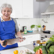 Senior or older woman with grey hair cooking in kitchen - fresh — Stock Photo
