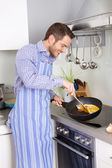 Happy man cooking egg omelet in the kitchen. — Foto de Stock