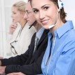 Telesales or helpdesk team - helpful woman with headset smiling — Stok fotoğraf #40244337