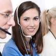 Telesales or helpdesk team - helpful woman with headset smiling — Stok fotoğraf