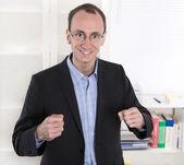 Succesvolle zakenman met pak en gesloten vuisten glimlachen op uit — Stockfoto