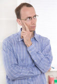 Pensive man with glasses touching chin. — Stock Photo