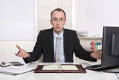 Questioningly bald engineer or specialist sitting at desk. — Stock Photo