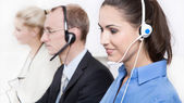 Telesales or helpdesk team with Headsets - workers at call Cente — Stock Photo