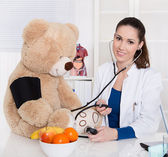 Pediatrician is measure blood pressure on a teddy bear. — Zdjęcie stockowe