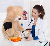 Pediatrician is measure blood pressure on a teddy bear. — Stock Photo