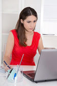 Attractive secretary in front of her computer at office. — Stock Photo