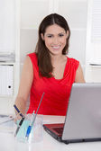 Aantrekkelijke secretaris achter haar computer op kantoor. — Stockfoto