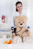 Occupation: Young female doctor with a teddy bear. — Photo