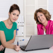 Two attractive businesswomen in front of notebook at office. — Stock Photo #40341173