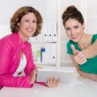Two successful smiling businesswomen with tablet-pc at desk at o — Stock Photo #40341207