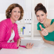 Two successful smiling businesswomen with tablet-pc at desk at o — Stock Photo