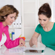 Teamwork: two colleagues working together with tablet-pc at desk — Stockfoto