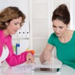 Teamwork: two colleagues working together with tablet-pc at desk — Stock Photo