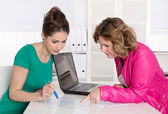 Teamwork at office with two attractive businesswomen. — Stock Photo