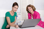 Two attractive businesswomen in front of notebook at office. — 图库照片
