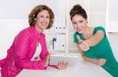 Two successful smiling businesswomen with tablet-pc at desk at o — Zdjęcie stockowe